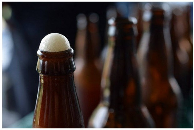 Fizz bubbles over from a home brewed, bottled beer. (Staten Island Advance/ Bill Lyons)